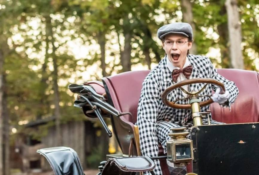 Man in plaid suit with hat and bowtie driving old buggy