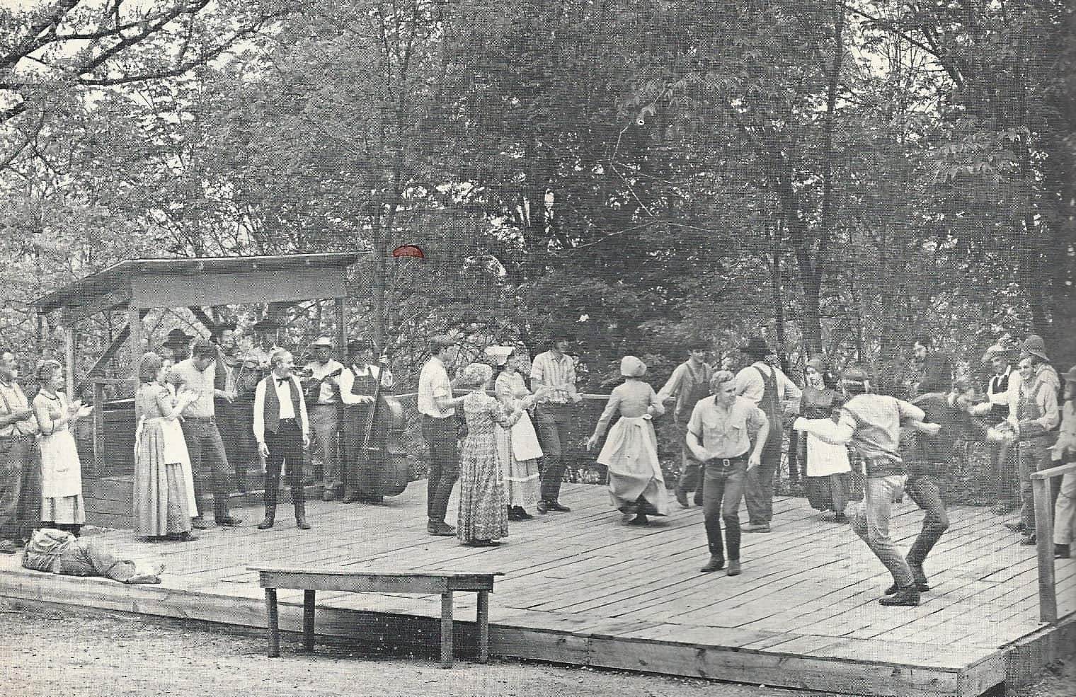Old photo of people dancing on wooden platform
