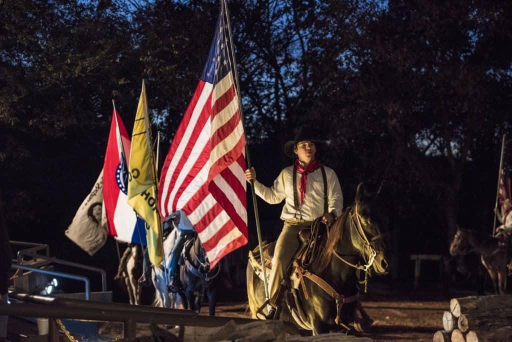 man holding American flag on horseback