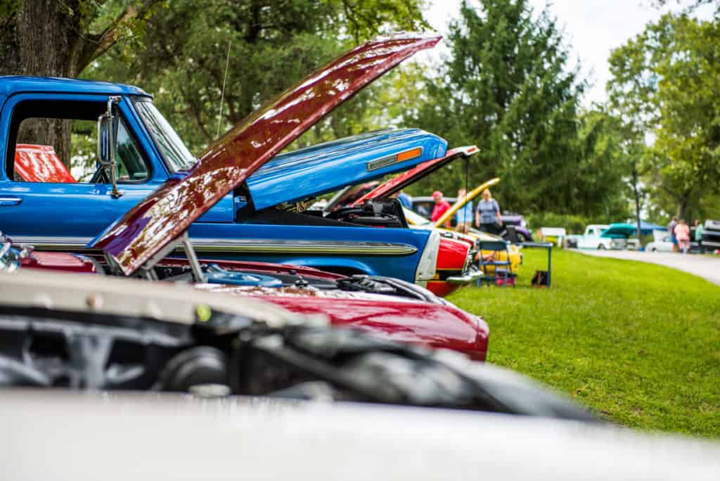 Classic cars lines up with their hoods open