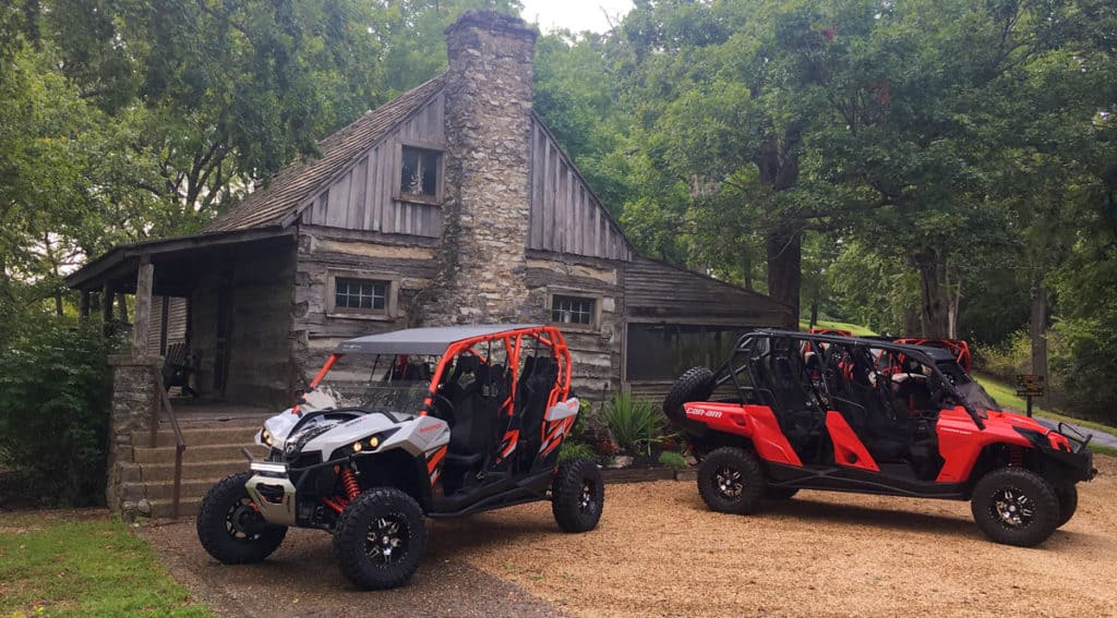 Two ATVs in front of an old cabin