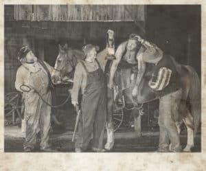 Rustic photo of people looking at dead man on horseback