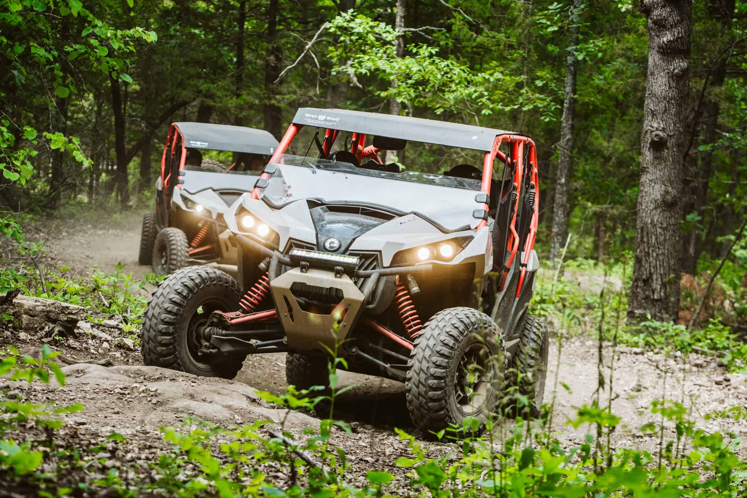 Two ATVs driving on gravel path through forest