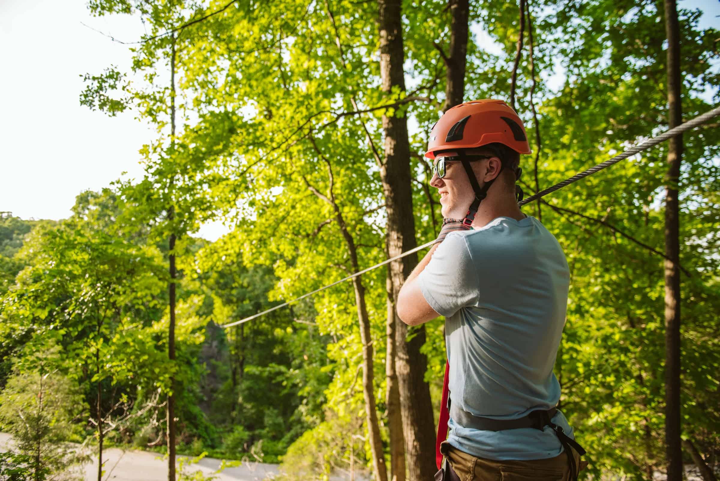 Man in orange helmet standing next to zipline in forest