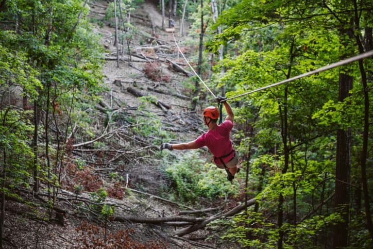 Man in orange helmet riding zipline through forest
