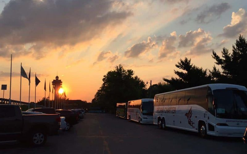 Tour busses lined up in parking lot at sunset