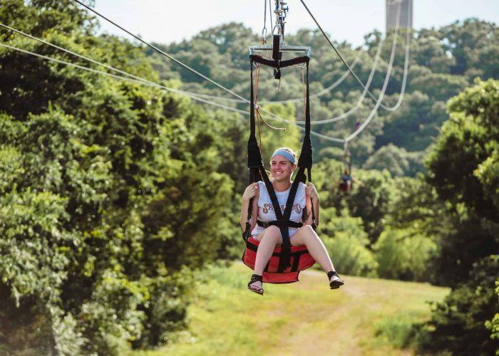 Woman wearing blue bandana riding zipline from tower