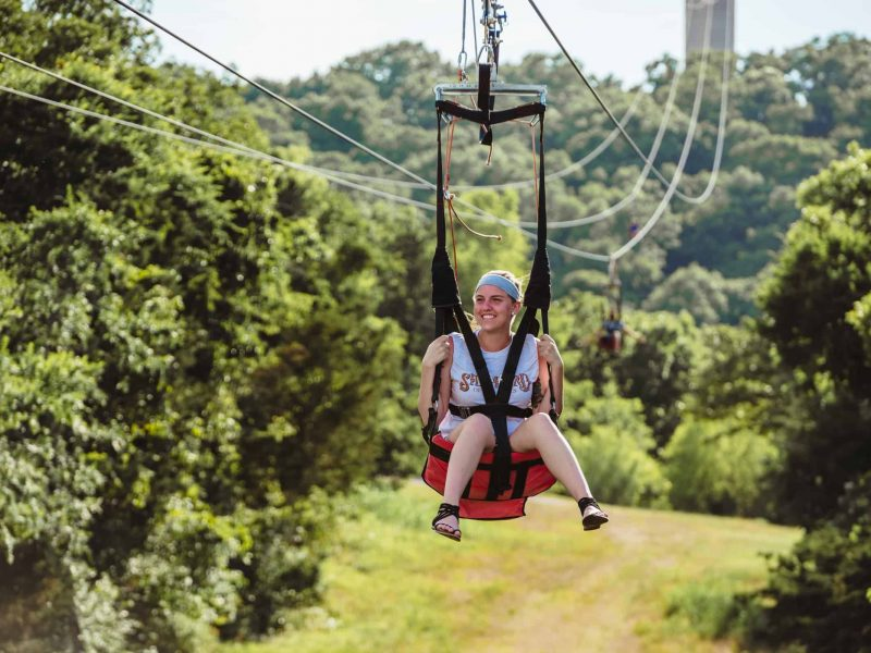 Woman wearing blue bandana riding zipline from tower