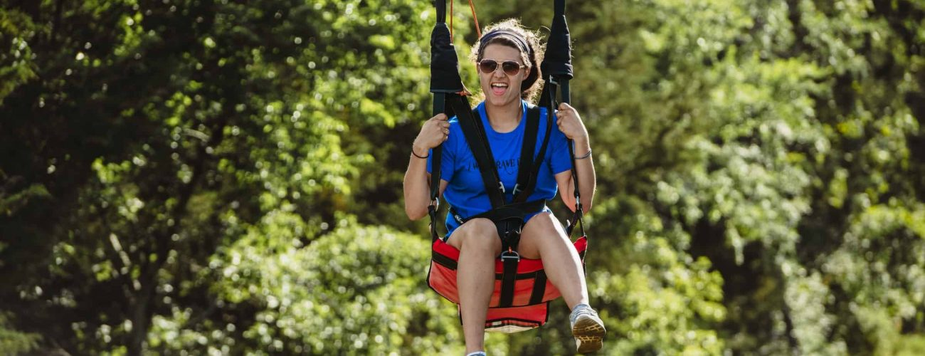 Woman wearing sunglasses and slicking tongue out riding zipline
