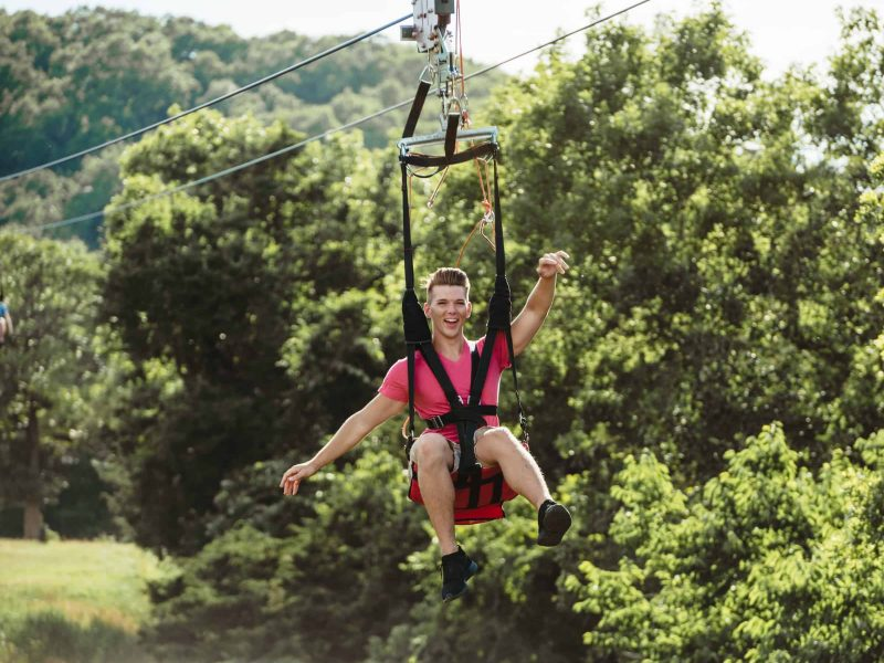 man sticking arms out riding zipline