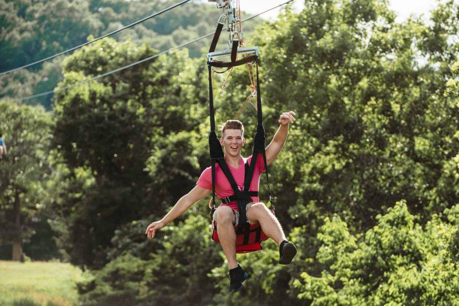 man sticking arms out riding zipline