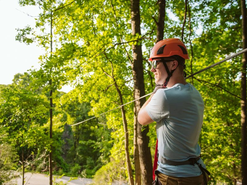 Man in orange helmet standing next to zipline in forest