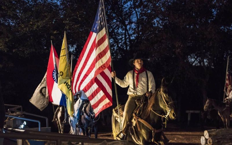 man holding American flag on horseback