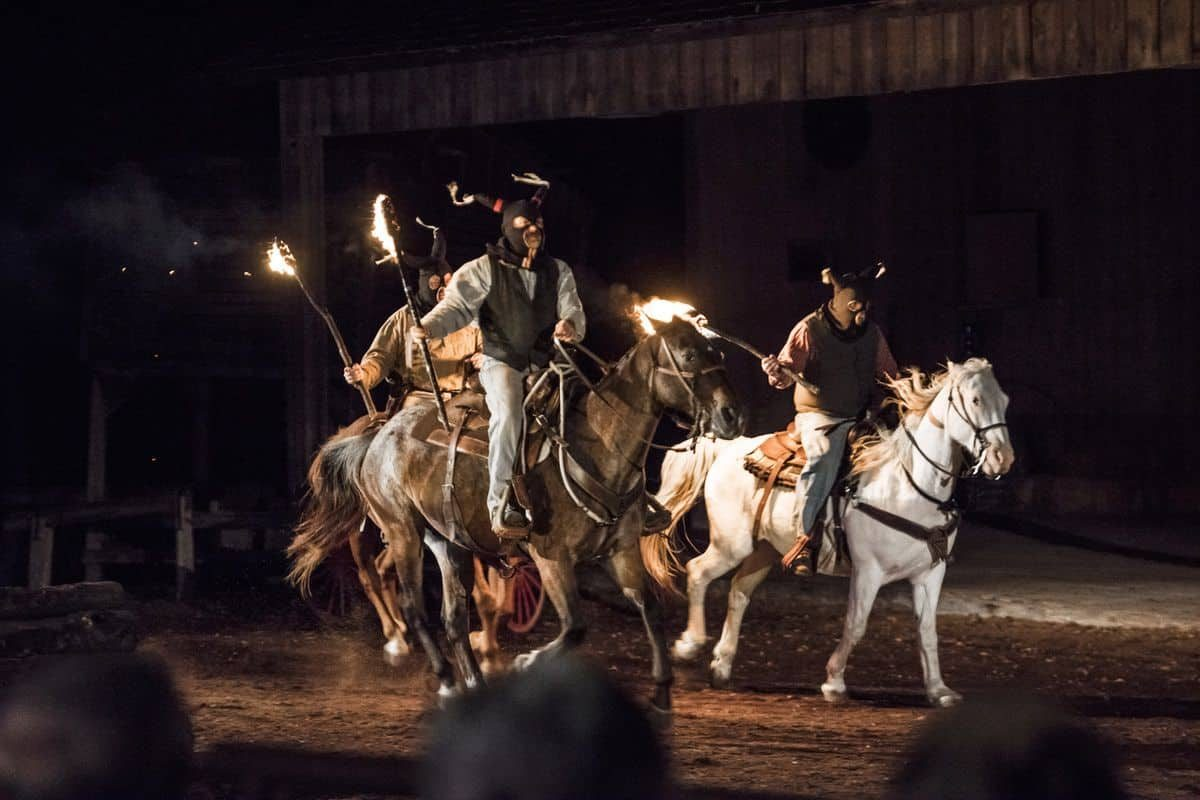 Men in masks holding torches on horseback