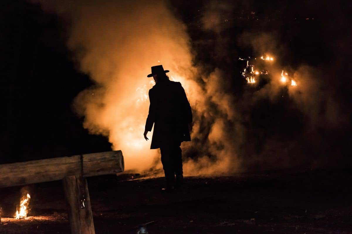 Silhouette of man in cowboy have in front of smoke and fire