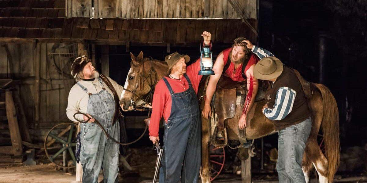 Three men inspect dead man on horseback