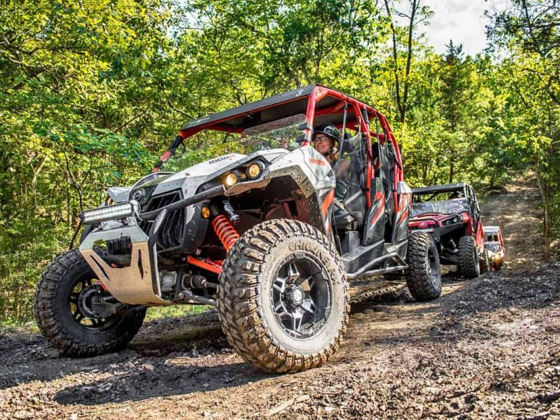 Three ATVs driving on dirt road through forest