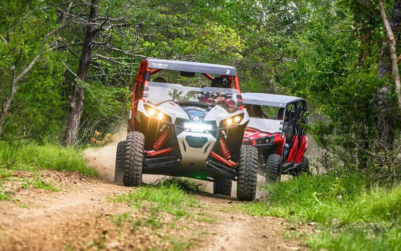 Two ATVs driving on dirt road through forest