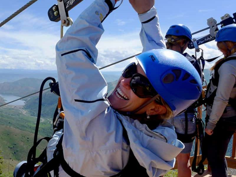 Woman in jacket and helmet about to zipline